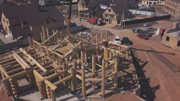 Luftaufnahme des neuen Holzhäuschen Bau im Gange, Arbeiter auf der Spitze der Holzsäulen und Baumaschinen im Sommertag. Clip. Prozess des Neubaus.