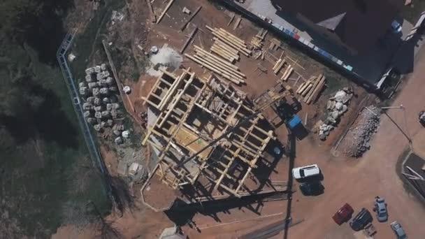 V letních dnech je zde výhled na stavbu nové dřevěné chalupy, stavební stroje, dělníky a stavební materiály. Klip. Proces nové stavební výstavby.