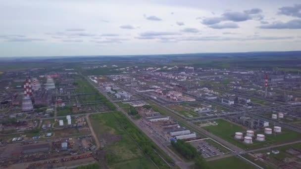 Letecký pohled na továrny a cisternové hospodářství pro volně ložené ropné a benzínové skladování. Klip. Velká průmyslová oblast nacházející se mimo město s poli a stromy na pozadí proti oblačnému nebi.