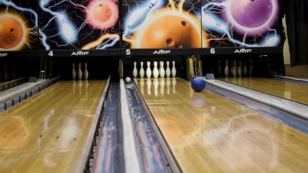 Modrá bowlingová koule valící se na trati v bowlingovém centru a srazit dolů bílé kolíky, volný čas a aktivní cport hry koncept. Média. Dřevěná bowlingová dráha a pohyblivá koule.