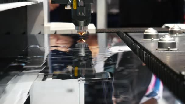 Automatický mechanismus řezání laserem pro kov na výstavní ploše, zblízka. Media. Elektronická zařízení a mechanismy jsou prezentovány na vědecké výstavě.