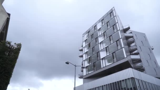 Unterseite des modernen Hauses mit Spiegelfassade. Aktion. moderne Designlösung in Glasfassade eines kleinen Hauses vor grauem Himmel