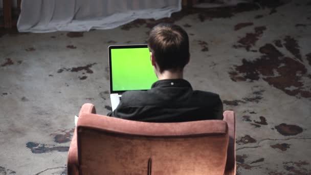 Nézd meg a hátsó fiatal férfi fekete inget ül a barna kényelmes széket, és dolgozik a laptop számítógép chroma kulcs zöld képernyőn. Stock Footage. A saját tartalom helye.