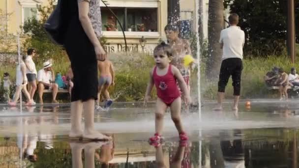 Frankreich, Paris - Juni 2019: Kinder planschen an heißen Tagen im Stadtbrunnen. Aktion. schönes kleines Mädchen, das im Stadtbrunnen läuft. Nasse Kinder kühlen sich an heißen Sommertagen im Brunnen ab