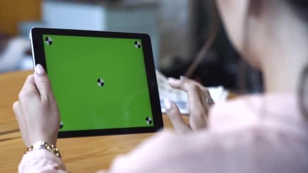 Pohled z ramene mladé ženy na růžovou košili sedící u stolu a klouzání na tabletu na zelené obrazovce Chromy. Skladní záběry. Obrazovka s klíčem Chroma pro umístění vlastního obsahu.