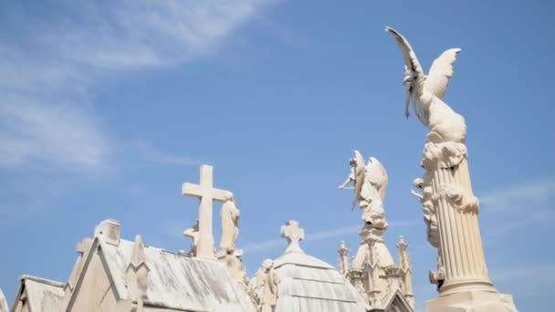 Angels and crosses on grave monuments in cemetery. Action. White stone sculptures and crosses tower on background of blue sky