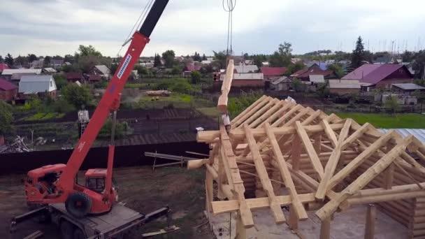 Horní pohled na stavbu dřevěných domů. Klip. Proces výstavby venkovského dřevěného domu na pozadí příměstské parcely. Dřevěná stavba domu se staviteli