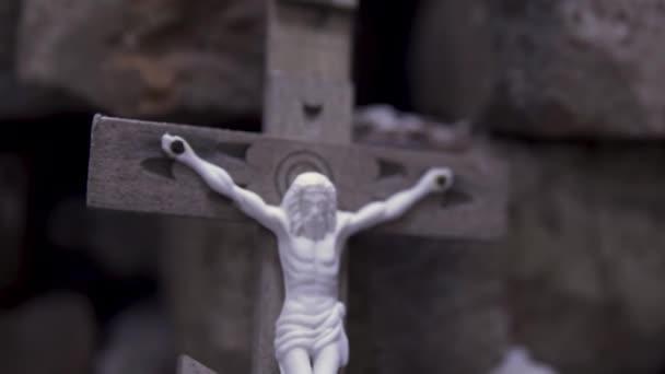 Közelről a fa kereszt keresztre feszített Jézus kő tégla háttér, Biblia és vallás koncepció. Felvétel. Az egyház vallási sajátossága, keresztény szimbolizmus.