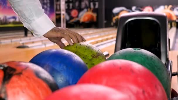 Zblízka pro muže ruku s míčem před házením ji při hraní bowling v bowlingovém klubu. Média. Sportovní a zábavní koncept, muž, který bere míč z regálu.