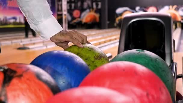 Zavřít pro muže ruku s míčem z regálu a hodit ho na bowling Lane. Média. Hráč hodí bowlingovou kouli, která srazí a kutálí.