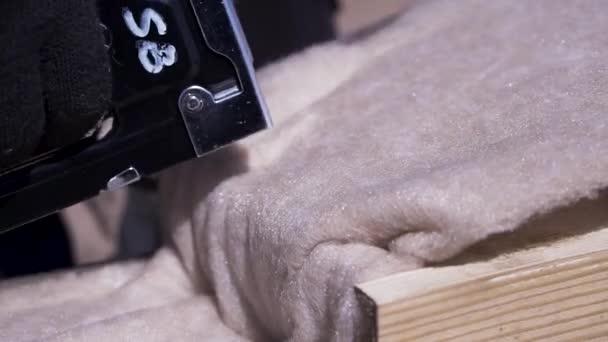 Zavřete ruce v ochranném skle, které jsou součástí tepelně izolačního materiálu a jsou vybaveny sešívačním sponerem k dřevěnému paprsku, konceptu domovní budovy. Klip. Profesionální truhlářské práce.