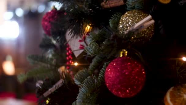 Nové roky míčky a Garland na rozmazané pozadí, koncept svátků. Rámeček. Vánoční skladba borového stromu, zlaté a červené vánoční kuličky, červené bobule.