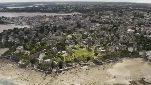 Stunning aerial view of the coastal big city with white houses and cottages located near the beach. Action. Modern city with beautiful architecture and the ocean shore.