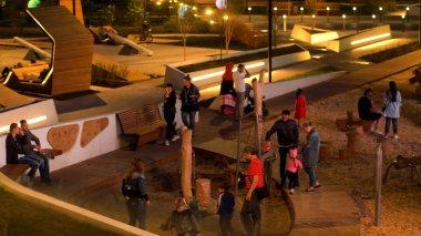 İnsanlar akşamları modern parkta vakit geçirirler. Stok görüntüleri. Şehir parkında sıradışı heykeller, banklar, sokak kucakları olan aileler.