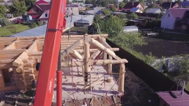 Instalace střešních trámů dřevěný dům. Klip. Horní pohled na stavbu dřevěného domu s dělníky a jeřábem na staveništi. Montáž fasádního rámu dřevěné střechy