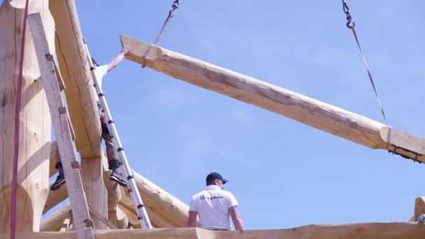 Crane with wood and working on construction site. Clip. Bottom view of process of construction of wooden building. Worker at construction site directs crane with log