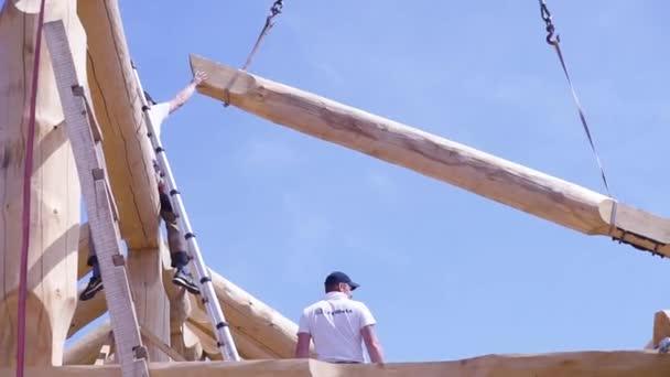 Jeřáb se dřevem a práce na staveništi. Klip. Dolní pohled na proces výstavby dřevěné budovy. Pracovník na staveništi řídí jeřáb s kmeny