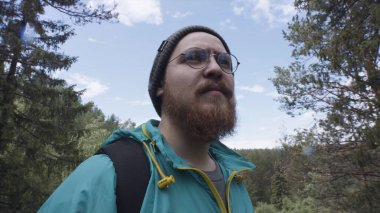 Close up of hipster hiker observing the the green valley on blue cloudy sky background. Stock footage. A bearded man with round glasses overlooking a beautiful forest.