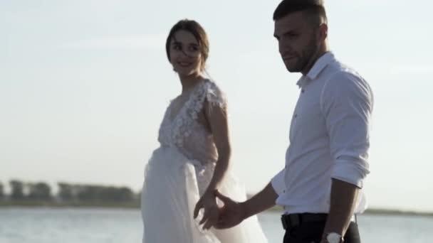 A menyasszony és a vőlegény sétálnak a folyóparton, egymás kezét fogva. Felvétel. Portré a menyasszony és a vőlegény tele szeretettel a háttérben a tó és a fényes ég.
