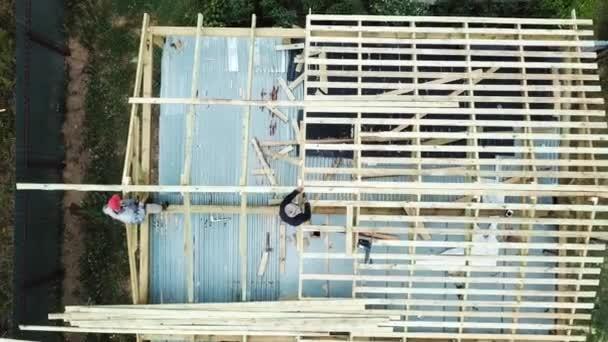Letecký pohled na dva starší muže, kteří v létě staví dřevěný rámový dům na své vlastní lokalitě. Záběry ze skladu. Stavební dělníci s vrtáky