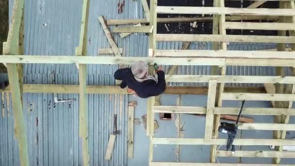 Luftaufnahme von zwei älteren Männern, die im Sommer an ihrem eigenen Standort ein Fachwerkhaus bauen. Archivmaterial. Bauarbeiter mit einem Bohrer