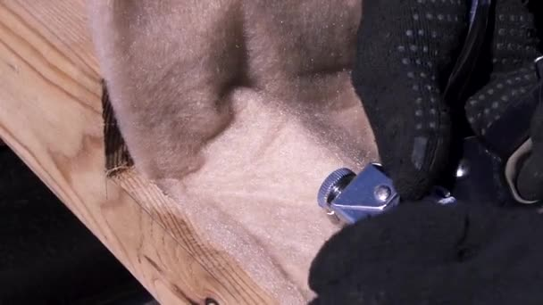 Close up of builder hands using construction stapler for nailing insulation to the wooden beam. Clip. Man hands in protective gloves while wooden house building.