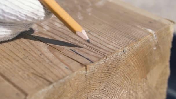 Detail měření a značení dřevěného nosníku tužkou. Klip. Tesař v bílých rukavicích značky na dřevěné tyči s tužkou a úhlovým pravítkem, dům stavební proces.
