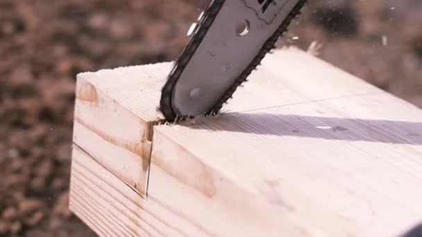 Detailní záběr pracovníka s elektrickou pilou řezání dřevěný trám s hoblinami a prach létající do stran. Klip. Tesařské práce, řezání dřevěné tyče pilou.