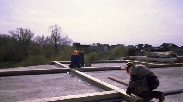 Rámcování střechy posádky, příprava dřevěné konstrukce, měření pro lepší přesnost. Klip. Pracovníci stojící na rovné střeše budovy a měřící dřevěný trám páskou.