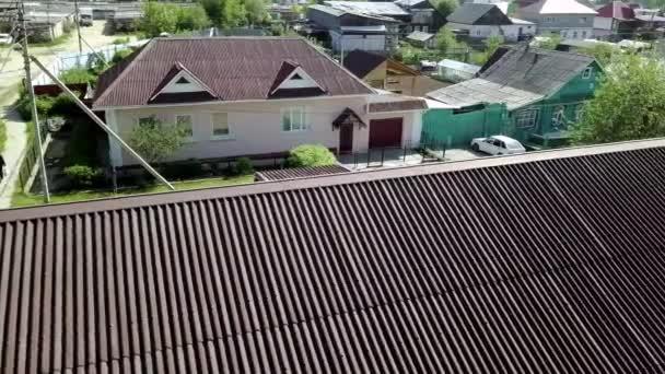 Nová střešní krytina na pozadí vesnice. Záběry ze skladu. Horní pohled na hřeben nové střechy na pozadí vesnických domů. Moderní tmavá střešní krytina venkovského domu