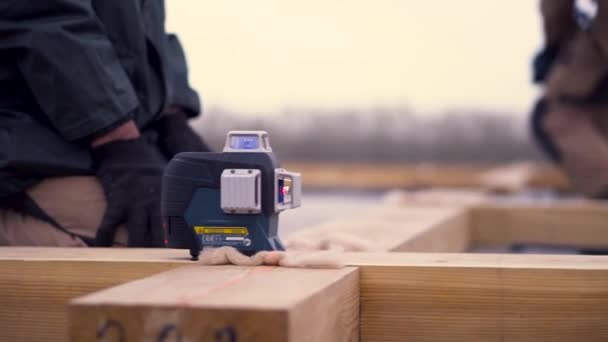 Close up of worker leveling wooden beam on construction site on bright cloudy sky background. Clip. Male builders making the wooden frame of the house.