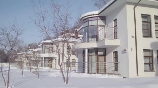Winterlandschaft mit Hütten, die in einer Reihe weißer Farbe vor blauem Himmel stehen. Archivmaterial. moderne schöne Häuser im verschneiten Winter