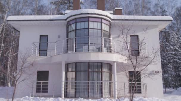 Fassade des schönen weißen modernen Design zu Hause im Winter auf schneebedeckten Bäumen und blauem Himmel Hintergrund. Archivmaterial. zweistöckiges Landhaus, architektonisches Konzept.