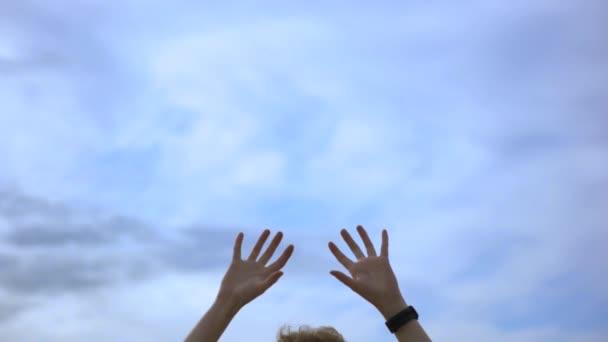 Menschenhände in die Luft gereckt auf blauem wolkenverhangenem Himmel, Freiheitsbegriff. Kunst. Mann mit Uhr am Handgelenk und Hand in der Luft.
