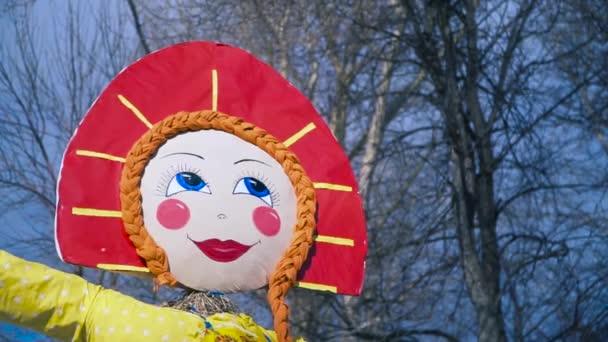 Slovanská oslava Shrovetide s tradiční podobiznou Slámy připravená k upálení. Klip. Dolní pohled na ženskou postavu v červeném kokoshniku na modrém pozadí oblohy.