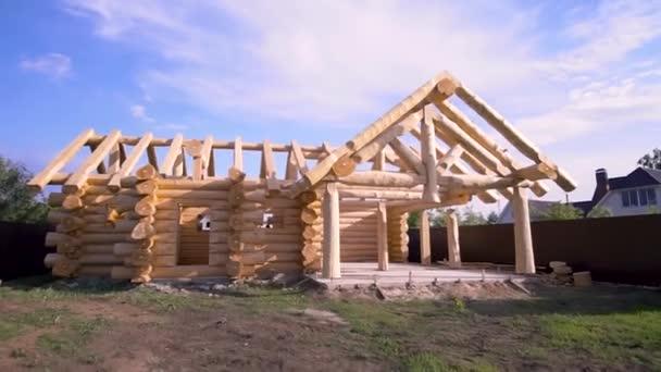 Hausneubau mit Holzhausrahmen auf hellblauem wolkenverhangenem Himmelshintergrund, Zimmereikonzept. Clip. unfertiges, ökologisches Holzhaus und Baugebiet.