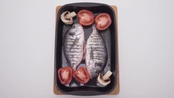 Dvě syrové ryby s kořením a zeleninou v podnosu na pečení. Akce. Krásné syrové ryby se zeleninou na pekárně před pečením v troubě. Vaření lahodné ryby v troubě