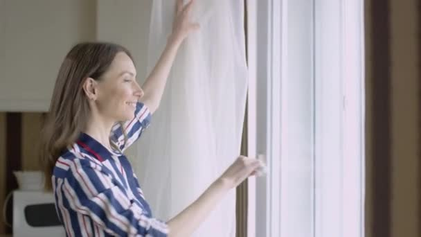 Beautiful woman looks out window happily. Video. Bright woman with smile looks out window watching children. Attractive mother happily watches her child from window