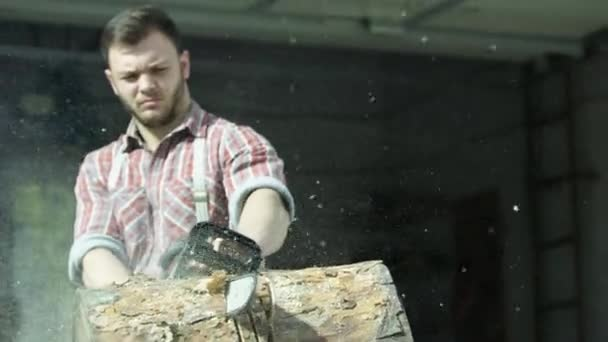 Portrait of caucasian young man worker sawing a log with a chainsaw. Video. Male carpenter sawing a part of tree trunk with wooden shavings flying into the sides.