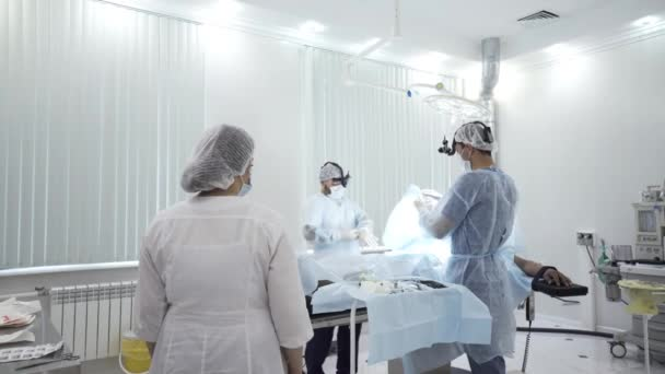 Team of doctors perform surgery while patient is under anesthesia. Action. View inside of the operating room with men surgeons, nurse, and sedated male patient.