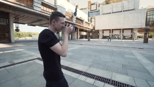 Mladý muž fotografuje populární budovy ve městě. Akce. Chlápek fotí moderní městskou architekturu. Fotograf fotí velkou budovu města