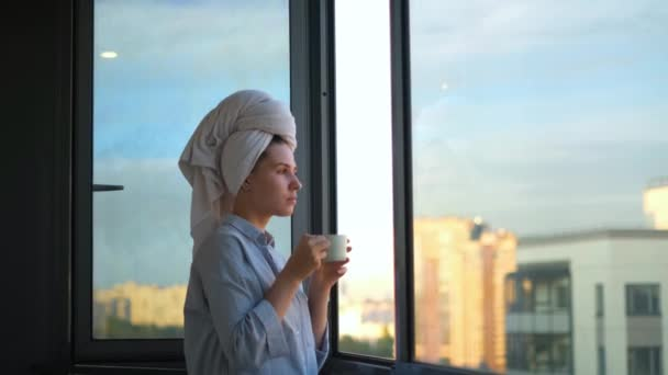 Mladá žena se ráno podívá z okna a vypije kávu. Koncept. Krásná žena začíná den s šálkem kávy a nádherný výhled z okna