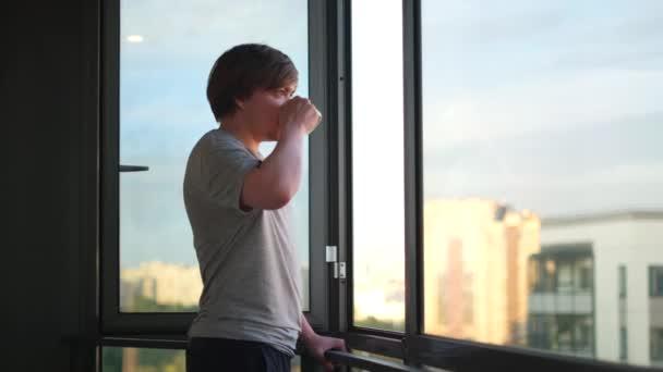 Boční pohled na šťastného mladého muže držícího šálek kávy na balkóně doma po ránu. Koncept. Muž pije čaj nebo kávu a stojí u otevřeného okna.