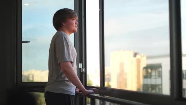 Šťastný muž na balkóně, dívající se do dálky otevřeným oknem. Koncept. Boční pohled na mladého blonďáka s výhledem na město.