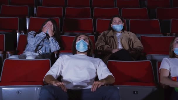 Lidi v kině se dívají na horor. Média. Sledování filmů v lékařských maskách během pandemie koronaviru. Lidé v maskách sledují strašidelné filmy