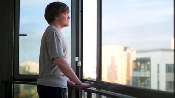 Dospělý muž v šedé tričku, stojící u otevřeného okna na balkóně a užívající si výhled. Koncept. Boční pohled na šťastného muže hledícího do nového dne otevřeným oknem doma.