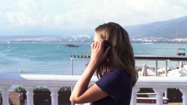 Mädchen genießen ihren Sommerurlaub an der Küste. Medien. Seitenansicht einer jungen schönen Frau, die in einem blauen T-Shirt auf blauem Meeresgrund den Damm der Stadt entlangläuft.