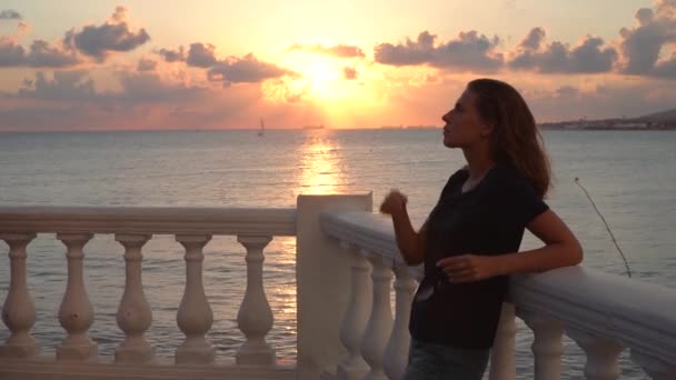 Attractive woman stands at railing on background of sunset. Media. Beautiful woman enjoys evening standing on embankment with view of sea horizon. Beautiful sunset with seascape