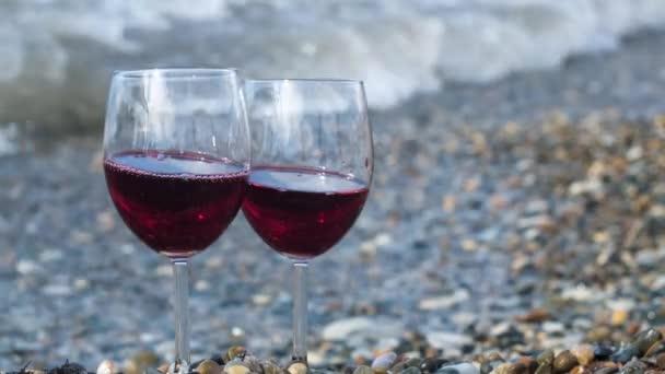 Romantikus nap egy pohár vörösborral a tengerparton egy napsütéses napon. Fogantatás. Két átlátszó pohár vörösborral a kavicsos strandon hullámokkal és tengerrel a háttérben.