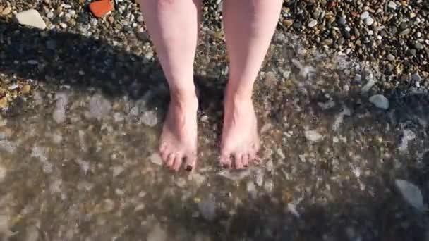 Horní pohled na nohy na pláži s mořskými vlnami. Koncept. Spojení s přírodou, krásné nohy a nohy ženy s nehty natřenými na černo je omýváno mořskými nebo oceánskými vlnami.